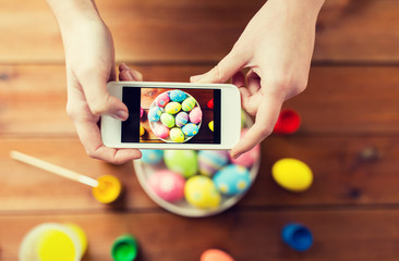 close up of hands with easter eggs and smartphone