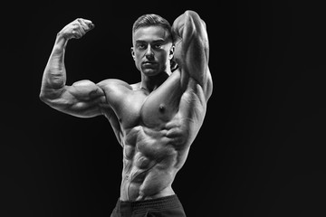 Bodybuilder with muscular physique looking at camera showing bic