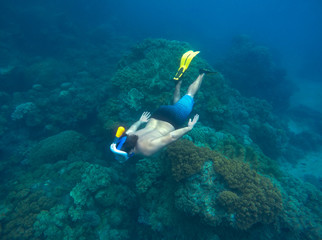 Man snorkeling in sea. Male snorkel in modern snorkeling gear - full-face mask and long fins.