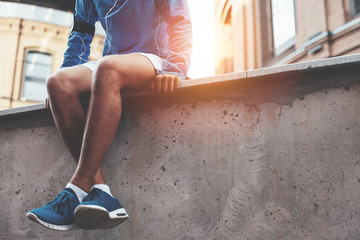 Male athlete in blue running shoes sitting and resting after street workout session at sunset