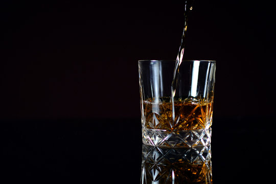Pouring Bourbon whiskey into glass