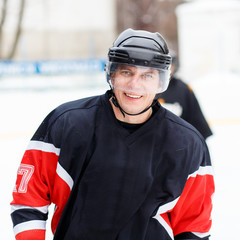 Young smiling ice hockey player in helmet and protective gear on ice hockey competition.