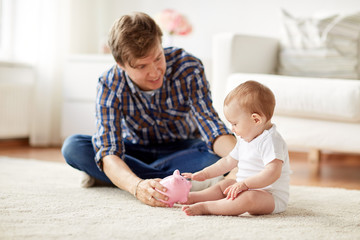 happy father with baby and piggy bank at home