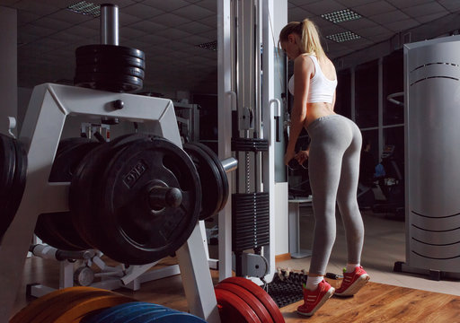 Sexy blond girl with a perfect figure and a great ass in gray leggings trains in fitness club