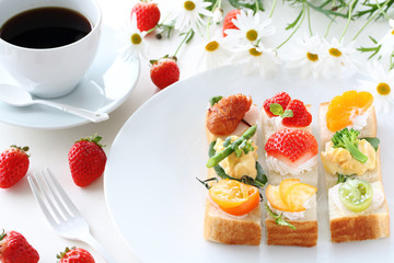 Various sandwiches with heart shaped strawberries on white plate 