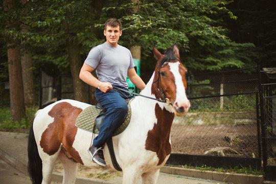 Portrait of happy man riding horse