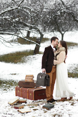 Old-fashioned couple in winter clouthes stands on snowed ground