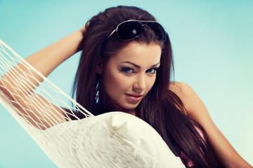 Beautiful woman in bikini relaxing in a hammock in vacation time