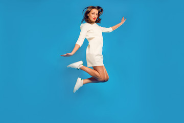 cheerful girl in a white dress and sneakers posing in a jump