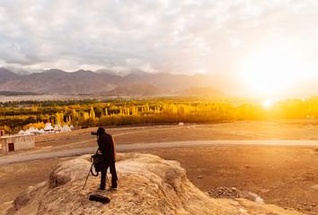 Photographer waiting the light for taking photograph in the himalaya range,  blur, soft focus: Leh, Ladakh, India.