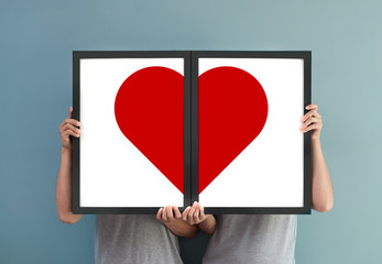 Couple holding red heart in picture frames.