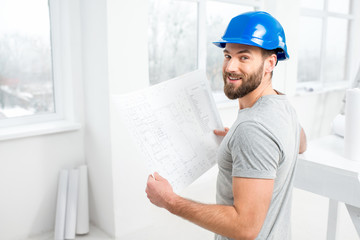 Handsome repairman or builder in helmet working with drawings on renovation of interior