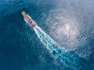 Aerial shot of the cargo ferry moving in an open tropical sea.