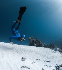 Wall Mural - Free diver hanging underwater over sandy sea bottom with rocks