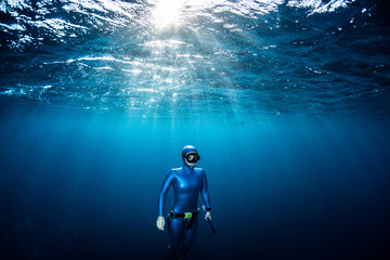 Wall Mural - Woman free diver ascending from the depth in a tropical clear sea