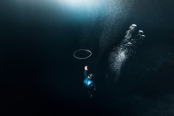 Wall Mural - Woman free diver chases bubble ring rising from the depth