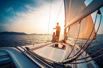 Couple enjoying sunset from the deck of the sailing boat moving in a sea Fotomurales