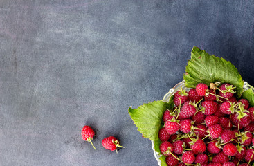 Close up ripe sweet raspberries in bowl on dark background. top view