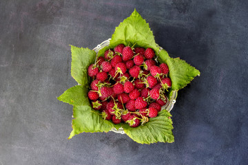 Ripe sweet raspberries in bowl on dark background. Close up, top view