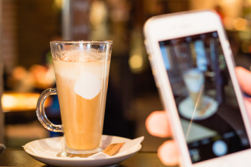 Taking picture of latte coffee with smartphone in cafe