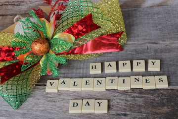 Happy Valentines day wording by crossword on old wooden board with beautiful ribbon background.