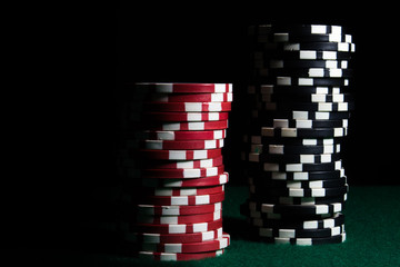 Stacks of red and black poker chips on a dark background