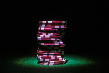 Stack of red poker chips in the spotlight on a dark background