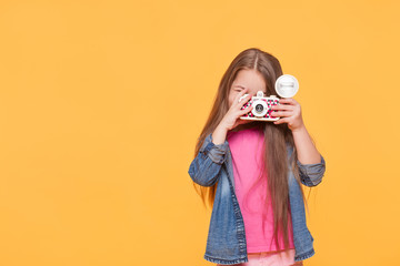 small child girl holding retro camera and taking photo