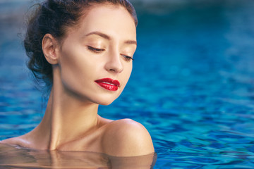 Relaxation and leisure. Beautiful young woman with red lips make-up enjoying suntan in swimming pool.