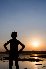 Silhouette of the boy stand with the sunset.
