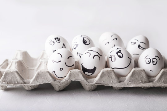 Eggs with funny faces in the package on a white background. Easter Concept Photo. Eggs. Faces on the eggs Eggs
