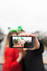 Young Couple Taking a Photo with a Mobile Phone for St Patrick D