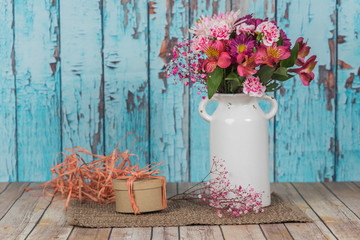Vintage vase with flowers and a gift wrapped in raffia