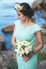 Bride in nature in the mountains near the water. Dress color Tif