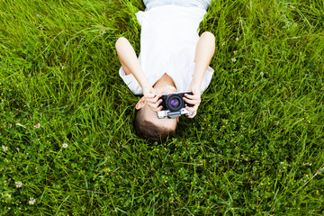 Little boy with retro photo camera shooting outdoor. Kid taking a photo using a film cam. Green summer garden. Young photographer.