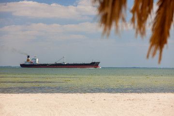 Oil Tanker Sailing Past Tropical Beach and Palm Tree