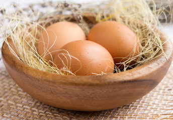 Chicken eggs in wooden plate closeup in rustic style