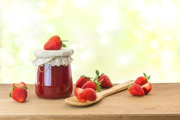 Erdbeermarmelade mit frischen Erdbeeren auf Holztisch
