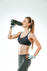 Muscular young woman athlete with a water on black