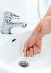 Plumber repairing sink with plumber's snake.