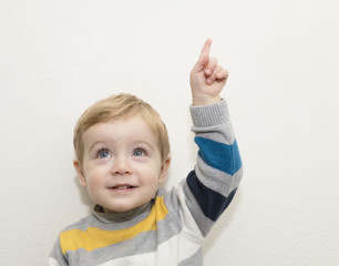 Funny child pointing up on white background