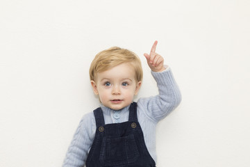Adorable little child pointing up on white background