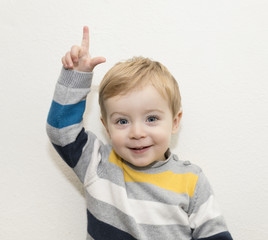 Adorable child pointing up on white background