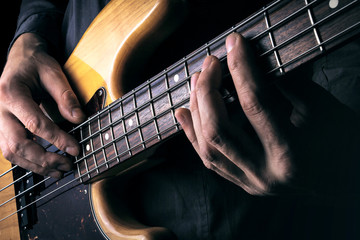 Rock music background, bass guitar player with selective focus