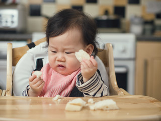 Asian baby girl eating bread first time