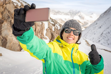 Active healthy smiling woman tanking selfie.with her phone camera doing thumbs up sign sharing with friends. Self picture of Fit female enjoying snow season vacations on the top of a snowy mountain.