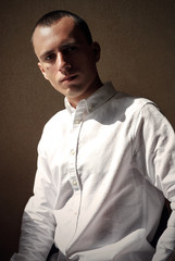 Young man in white polo t-shirt on warm background