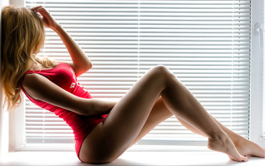 Fototapeta Caucasian blonde girl posing near a window at home or office. Sexy woman with curly hair style, long legs and hot body. obraz