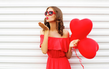 Portrait woman in red dress sends air kiss with balloon heart sh