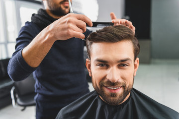 Joyful young guy attending hairdressers